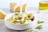 Eingelegter Feta in Olivenöl mit Knoblauch, Frühllingszwiebeln, Thymian, Rosmarin und Zitronenpfeffer