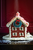 A gingerbread house being sprinkled with sugar