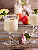 Creamy, cold apple milkshake with vanilla ice cream in glasses