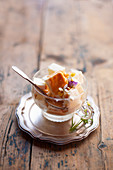 Vanilla ice cream with caramel sauce and viola flowers