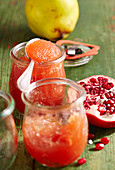 Jars of quince and pomegranate jam with a silver spoon