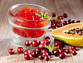 Papaya-Cranberry-Konfitüre im Glas auf Holzuntergrund
