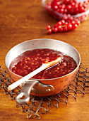Homemade melon and redcurrant jam in a copper pan