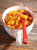Spicy papaya and pineapple chutney with ginger, chilli and vinegar in a ceramic cup