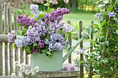 Gießkanne mit Fliederstrauß am Gartenzaun