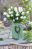 Weißer Tulpenstrauß in Blechkanne, Kränzchen aus Gras als Dekoration