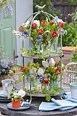Etagere mit Sträußen aus Tulpen, Flieder, Akelei, Rosen und Wolfsmilch