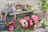 Frisch geschnittene Blüten von Pfingstrose in Holzkiste und kleiner Rosenstrauß auf dem Topftisch