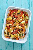 Chicken, shrimp, chorizo and Mediterranean vegetables with saffron and tomato sauce in a tray