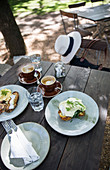 Summer breakfast al fresco with eggs Benedict and cappuccinos