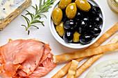 Mediterrane Vorspeisenplatte mit Käse, Lachs, Oliven und Brotsticks