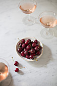 A bowl of cherries next to glasses of champagne