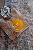 A glass of orange juice with flowers