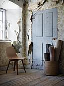 Holzstuhl und aufgerollte Teppiche im Zimmer mit abgeblätterte Tapete