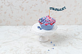 A cupcake with raspberry cream and forget-me-nots