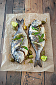 Baked sea bass with caper apples on a baking tray