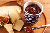 Homemade fig chutney served with cheese on a wooden board