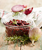 Homemade fig and cherry chutney with rosemary in a glass jar
