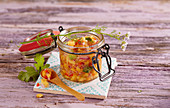 Fruity and sour papaya salsa in a glass jar