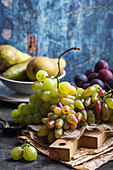 Fresh ripe grapes on wooden cutting board, pears and plums in bowls, wooden rustic background