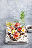 Close-up of sandwich with dark rye bread, cream cheese, salmon, onion, capers, boiled egg