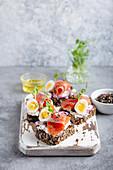 Dunkles Roggenbrot mit Frischkäse, Lachs, Zwiebel, Kapern und Ei