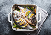 Baked fish dorado with green asparagus in white ceramic baking pan on gray rustic concrete background