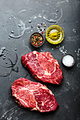 Close-up of raw marbled meat steak Ribeye on black rustic stone background with seasonings, olive oil