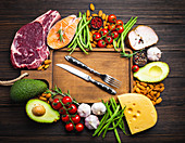 Knife and fork over wooden cutting board and ketogenic low carbs ingredients for healthy eating concept and weight loss