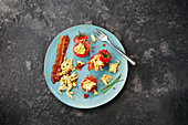 Stuffed cherry tomatoes with crispy bacon and scrambled eggs