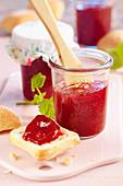 Dreifrucht-Konfitüre aus Mango, Himbeeren und Erdbeeren im Glas und auf Brot