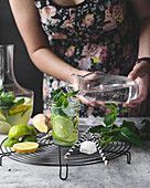 Infused water with lemon, lime, ginger and mint. woman pouring water