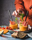 Melonen-Gazpacho mit Schinken und Minze anrichten