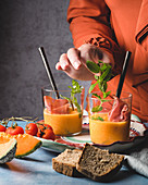 Woman puts mint on melon gazpacho