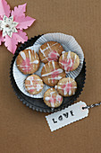 Gluten-free biscuits with pink frosting and a label saying 'Love'