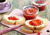 Strawberry and banana jam in jars and on slices of buttered bread