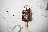 Crashed vanilla and chocolate ice cream popsicle on a marble surface