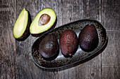 Avocados in and beside a ceramic bowl
