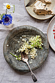 Elderflower in a stone bowl next to halva on a dessert plate