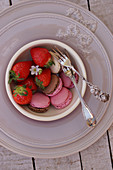 Various macarons and fresh strawberries in small bowls on a place setting