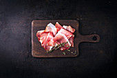 Raw ham and thyme on a cutting board