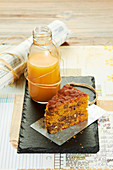 A slice of carrot cake with orange juice