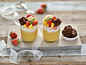 Vegan mango millet pudding with coconut yoghurt, mango and strawberry salad, oatmeal brownies and cashew cream