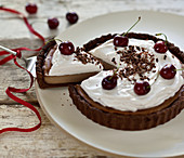 Vegan nougat cheesecake with cream topping and fresh cherries