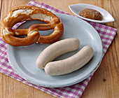 A pair of white sausages with pretzel and sweet mustard (snack, Bavaria)
