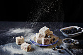 Blueberry marshmallows being dusted with icing sugar