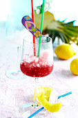 A mocktail in a wine glass with grenadine, sour cherries, lemon and pineapple