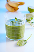 A green smoothie made with banana, apple, spinach, cucumber, ginger, lime and coconut milk