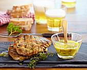 Grilled pork steaks in a herb and mustard marinade, beer and white bread