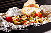 Grilled Mediterranean vegetables with a herb marinade in aluminium foil with sheep's cheese and white bread